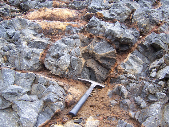 Pillow lavas with a hammer for scale. Notice the radial joints. The pillows are surrounded by brown, altered glass.