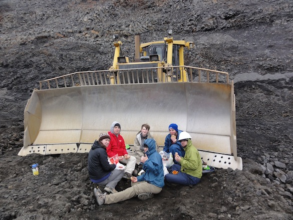 The students celebrated the completion of their mission with lunch by large mining equipment.