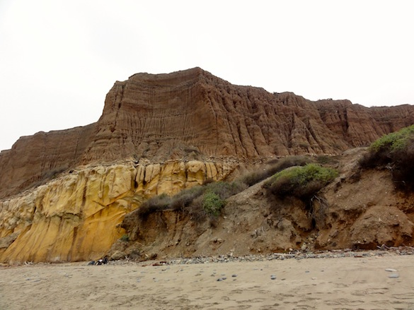 The fantastic cliffs along San Onofre Beach consist of the late Miocene San Mateo sandstone overlain by much younger alluvial sediments. Notice the bags on beach for scale.