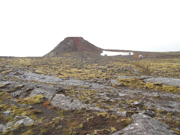 View of Thrihnukagigur Cone and the Inside the Volcano hut (at the base to the right) from the surrounding lava fields. Photo Credit: Ellie Was