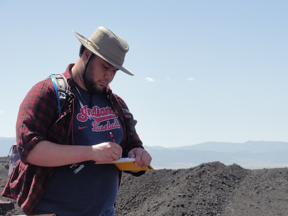 Kyle Burden ('14), shown here taking careful notes, will be working on the welded bomb wall using an approach similar to the one Team Iceland used on pillow lavas. He'll be collecting high-resolution images with a GigaPan and making careful measurements of bombs across the exposure.