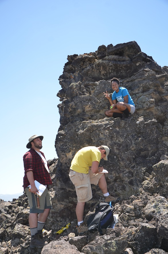 Kyle, Ben, and Candy document the stratigraphy of an isolated lava pillar in the middle of a depression. Credit: T. Wilch