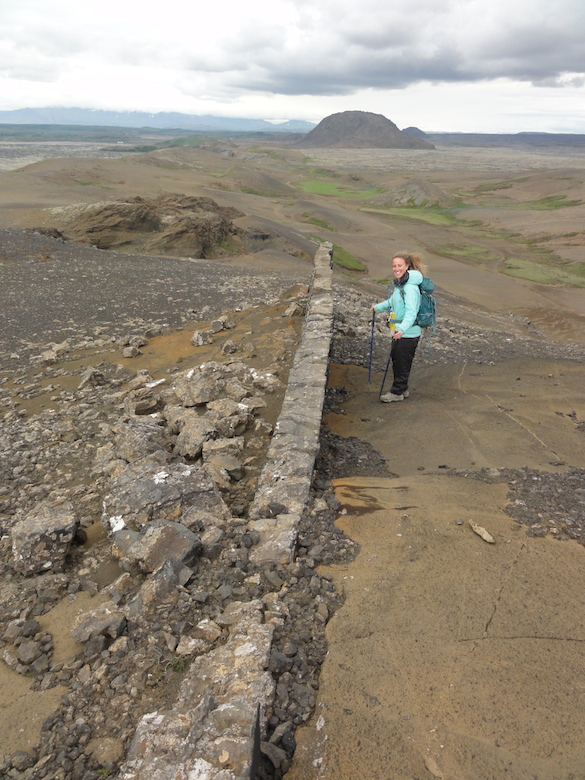 Cara Lembo ('17, Amherst) stands next to a ridge-parallel dike intruding through a tephra cone. Helgafell, a hyalocastite edifice, is in the distance.